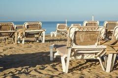 Loungers Солнця и закрытые зонтики на курорте на море, спокойной и расслабленной атмосфере летнего отпуска на заходе солнца Стоковые Фотографии RF