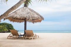 Loungers Солнця на белом тропическом пляже около голубого океана подпирают Стоковая Фотография