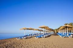 Loungers Солнця на пляже в Марбелье Стоковое Изображение