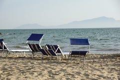 Loungers Солнця опорожняют на курорте на море, спокойной и расслабленной атмосфере летнего отпуска на заходе солнца Стоковая Фотография
