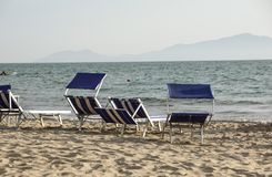 Loungers Солнця опорожняют на курорте на море, спокойной и расслабленной атмосфере летнего отпуска на заходе солнца Стоковые Изображения RF