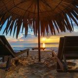 Loungers Солнця с зонтиком на пляже, восходом солнца Стоковое Фото