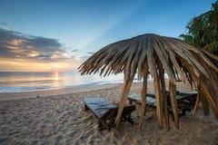 Loungers Солнця с зонтиком на пляже, восходом солнца Стоковые Фото