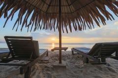Loungers Солнця с зонтиком на пляже, восходом солнца Стоковое Изображение RF