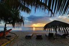 Loungers Солнця с зонтиком на пляже, восходом солнца Стоковые Изображения RF