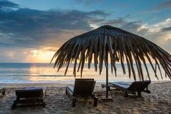 Loungers Солнця с зонтиком на пляже, заходом солнца Стоковое фото RF