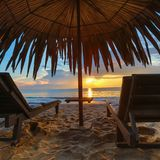 Loungers Солнця с зонтиком на пляже, заходом солнца Стоковые Изображения RF