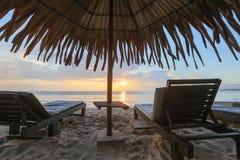 Loungers Солнця с зонтиком на пляже, заходом солнца Стоковая Фотография RF