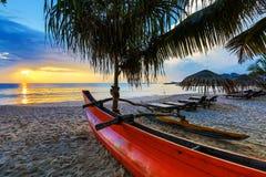 Loungers Солнця с зонтиком на пляже, заходом солнца Стоковая Фотография
