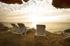 3 loungers солнца на пляже с заходом солнца на заднем плане Стоковое Фото