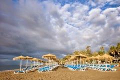 Loungers Солнця на пляже Марбельи Стоковые Изображения