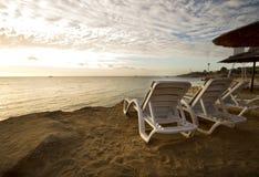 Loungers Солнця на пляже с заходом солнца на заднем плане Стоковое Фото