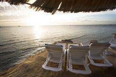 Loungers Солнця на пляже с заходом солнца на заднем плане Стоковые Изображения