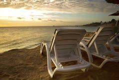 Loungers Солнця на пляже с заходом солнца Стоковые Изображения