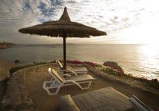 Loungers Солнця на пляже с заходом солнца Стоковые Изображения RF