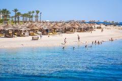 Loungers Солнця с зонтиками на пляже Стоковые Изображения