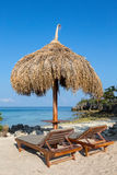 Loungers Солнця с зонтиком соломы на пляже Стоковые Изображения RF