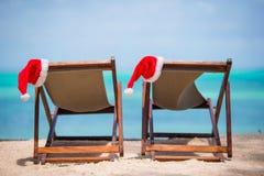 Loungers Солнця с шляпой Санты на красивом тропическом пляже с белыми песком и бирюзой мочат Стоковая Фотография RF