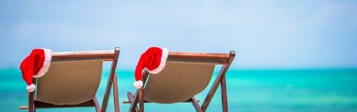 Loungers Солнця с шляпой Санты на тропическом пляже с белыми песком и бирюзой мочат Стоковое Изображение RF