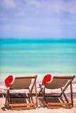 Loungers Солнця с шляпой Санты на тропическом пляже с белыми песком и бирюзой мочат Стоковые Изображения RF