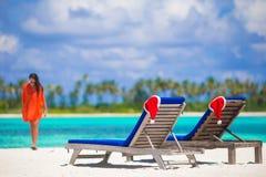 2 loungers с красными шляпами Санты на тропической белизне Стоковое фото RF