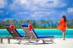 2 loungers с красными шляпами Санты на тропической белизне Стоковые Фотографии RF