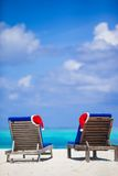 2 loungers с красными шляпами Санты на тропическом пляже Стоковые Изображения