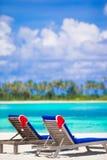 2 loungers с красными шляпами Санты на тропическом пляже Стоковые Фотографии RF