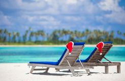 2 loungers с красными шляпами Санты на тропическом пляже Стоковое Изображение