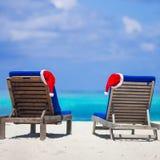 2 loungers с красными шляпами Санты на тропическом пляже Стоковые Изображения RF
