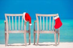 2 loungers с красными шляпами Санты на тропическом пляже Стоковое фото RF
