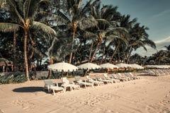 Loungers с парасолями на пляже Стоковые Фото