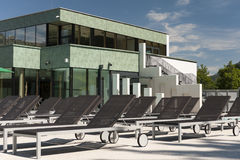 Loungers arranjados do sol na frente de um moderno novo Fotos de Stock
