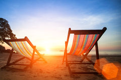 Loungers on the beach deserted oceanside. At amazing sunrise Royalty Free Stock Images