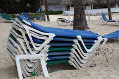 Loungers on the beach. / A stack of sun beds on the beach royalty free stock photography
