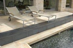 Loungers de Sun em uma piscina Foto de Stock Royalty Free