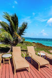 Loungers on the deck by the seafront Tobago Caribbean.  royalty free stock photography