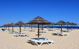 Loungers del sole e del parasole sulla spiaggia del Algarve immagine stock