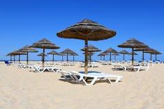 Loungers del sole e del parasole sulla spiaggia del Algarve fotografia stock