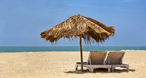 Loungers desserted beach blue sky Royalty Free Stock Photography