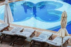 Loungers di Sun intorno ad una piscina fotografia stock