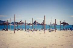 Loungers e guarda-chuvas da praia na praia imagens de stock