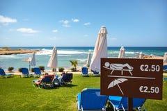 Loungers e guarda-chuvas Quanto faz o custo das férias imagens de stock royalty free