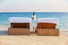 Loungers At Edge Of Tropical Sea With Champagne Bucket Royalty Free Stock Images