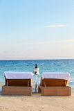 Loungers At Edge Of Tropical Sea With Champagne Bucket Royalty Free Stock Photography