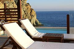 Loungers in front of pool and sea royalty free stock photos