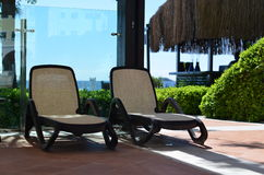 Loungers in hotel. Loungers near the pool on the background of the sea Stock Images