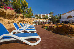 Loungers near the pool, luxury buildings and palm trees behind Royalty Free Stock Photography