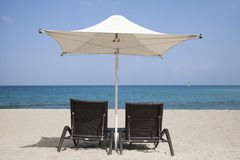 Loungers with parasol. Two chaise loungers under a white parasol in front of a blue sea Royalty Free Stock Images