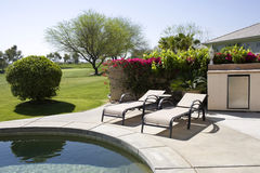 Loungers by the pool. Two loungers by the side of a swimming pool with a view of the golf course Stock Photos